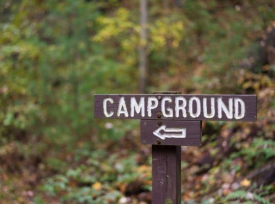 closeup-of-a-wooden-campground-sign-with-arrow-alo-RFTU6YC.jpg